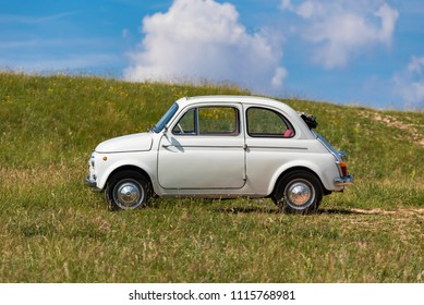 Italy, Rome – 17 June 2018: Italian historic car, Fiat 500, car parked in a meadow in the countryside, blue sky background,