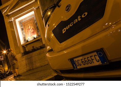 Italy, Rome, August 6, 2011: Fiat Ducato with the number 666 on the background of the image of the Madonna and Child at night. Long exposure.
