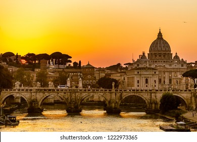Italy. Rome. Sunset over the Tiber and Bridge of Angels (Ponte Sant'Angelo) in the foreground. There is the Vatican City with St. Peter's Basilica in the background