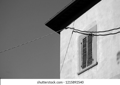 Italy, a section of an house facade with a wooden window and dangling electric wires