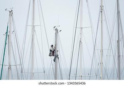 Italy, Siciliy, Mediterranean sea, Marina di Ragusa, 19 March 2019, man working up a sailing boat mast in the marina - EDITORIAL