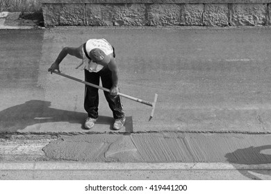 Italy, Sicily; 12 May 2016, man at work fixing a road - EDITORIAL