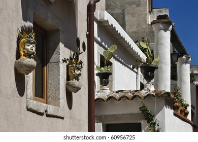 Italy, Sicily, Castelmola (Taormina), old buildings with ornamental sicilian statues and prickly pears