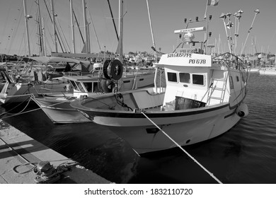 Italy, Sicily, Marina di Ragusa (Ragusa Province), 11 October 2020, sicilian wooden fishing boats and luxury yachts in the port - EDITORIAL