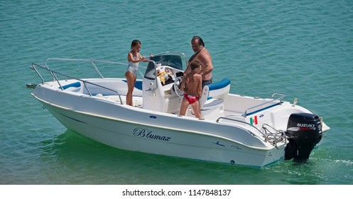Italy, Sicily, Mediterranean Sea, Marina di Ragusa; 2 August 2018, people on a motor boat in the port - EDITORIAL