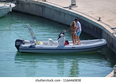 Italy, Sicily, Mediterranean Sea, Marina di Ragusa; 28 August 2018, couple on a rubber boat in the port - EDITORIAL