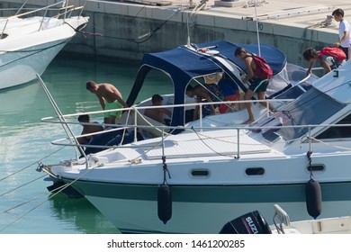 Italy, Sicily, Mediterranean Sea, Marina di Ragusa (Ragusa Province); 25 July 2019, people on a motor boat and luxury yachts in the port - EDITORIAL