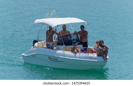 Italy, Sicily, Mediterranean Sea, Marina di Ragusa (Ragusa Province); 10 August 2019, people on a motor boat in the port - EDITORIAL