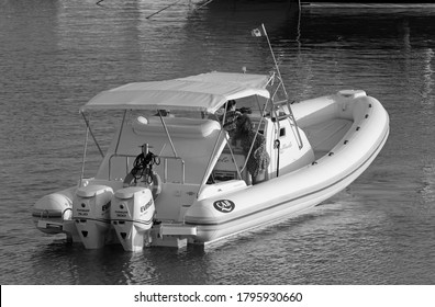 Italy, Sicily, Mediterranean Sea, Marina di Ragusa (Ragusa Province); 12 August 2020, people on a rubber boat and luxury yachts in the port - EDITORIAL