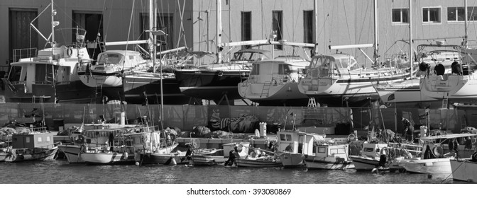 Italy, Sicily, Mediterranean sea, Marina di Ragusa; 18 March 2016, wooden fishing boats and luxury yachts ashore in a boatyard in the marina.