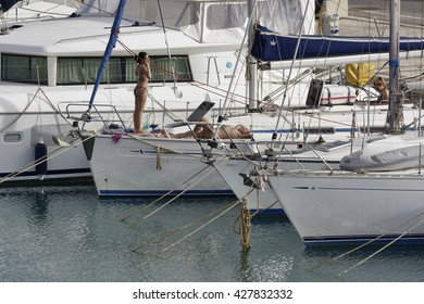 Italy, Sicily, Mediterranean sea, Marina di Ragusa; 28 May 2016, people relaxing on a sailing boat in the port - EDITORIAL