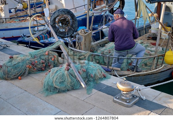 Italy, Sicily, Mediterranean sea, Marina di Ragusa; 20 December 2018, fisherman cleaning his nets on a fishing boat in the port - EDITORIAL
