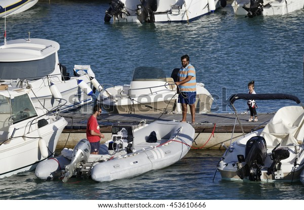Italy, Sicily, Mediterranean sea, Marina di Ragusa; 16 July 2016, people on the jetty with boats and luxury yachts in the port - EDITORIAL