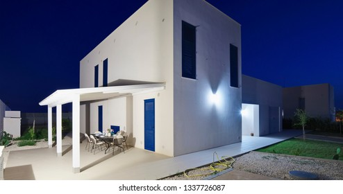 Italy, Sicily, Ragusa Province, countryside; 19 May 2018, elegant private house, view of the facade and the patio with a dining table at sunset - EDITORIAL