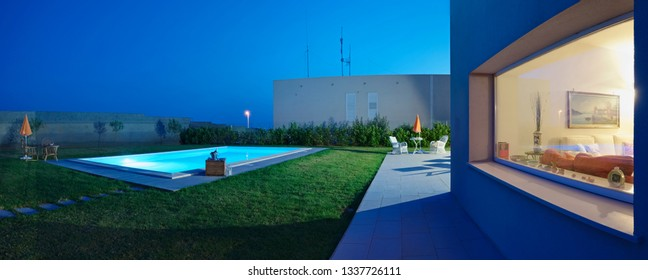 Italy, Sicily, Ragusa Province, countryside; 19 May 2018, elegant private house, view of the facade and the swimming pool in the garden at sunset - EDITORIAL