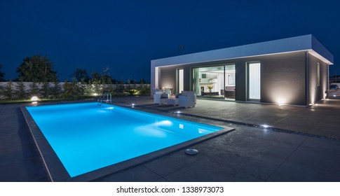 Italy, Sicily, Ragusa Province, countryside; 26 May 2018, elegant private house, view of facade, the swimming pool and the garden at sunset - EDITORIAL