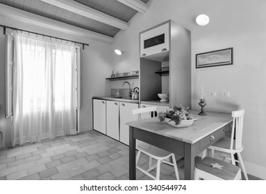 Italy, Sicily, Ragusa Province, countryside; 1 August 2015, elegant private house, kitchen with a dining table - EDITORIAL