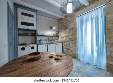 Italy, Sicily, Ragusa Province, countryside; 2 August 2015, elegant private house, kitchen with a wooden table - EDITORIAL