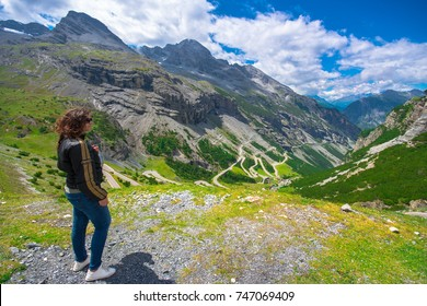 Italy, Stelvio National Park. Woman moto biker enjoys the view at the famous road to Stelvio Pass in Ortler Alps. Alpine landscape on July 11, 2017.