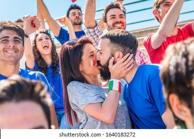 Italy supporters celebrating at stadium with flags - Couple kissing in the crowd of fans watching a match and cheering team Italy - Sport and lifestyle concepts