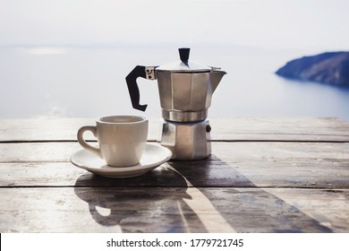 Italy travel, cup of coffee and moka machine maker on a table over blue sky and sea. Summer holiday, italian vacations concept