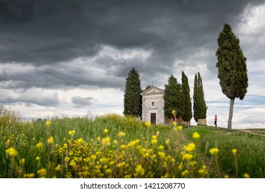 Italy Tuscany - April 20,2019. Cappella Di Vitaleta or Vitaleta Chapel near San Quirico D'Orcia in Tuscany. Yellow rapeseed flowers with the famous Chapel on background with posing woman