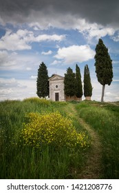 Italy Tuscany - April 20,2019. Cappella Di Vitaleta or Vitaleta Chapel near San Quirico D'Orcia in Tuscany. Yellow rapeseed flowers with the famous Chapel on background