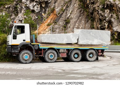 Italy, Tuscany, Apuan Alps, Carrara. 13th of June 2018. Side view of a heavy truck loaded with two gray marble blocks.