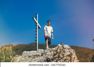 Italy Tuscany, young man is standing next to a summit cross