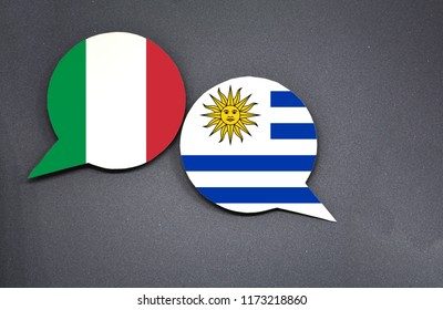 Italy and Uruguay flags with two speech bubbles on dark gray background