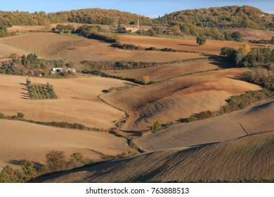Italy. Val d'Orcia in Tuscany, central Italy, province of Siena, Monticchiello. View from town over harvested fields.