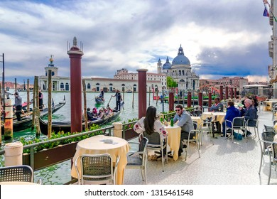 ITALY, VENICE APRIL 19, 2017: A street cafe on a grand canal in the background of the Church of Santa Maria in Venice