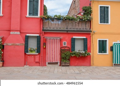 Italy. Venice. Burano.Color houses.Red and yellow house with a door and a balcony.5,september, 2016.