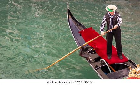 ITALY, VENICE - FEB 7, 2013: Gondolier on a gondola on the Grand Canal in Venice. Gondola's are a major mode of touristic transport in Venice, Italy