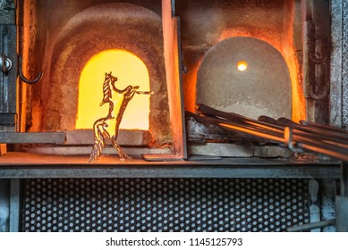 Italy, Venice, glass horse and Murano factory special glass-blowing tools: red-hot furnace with fire to make the glass malleable, and iron rods (pontello). Traditional Italian craftsmanship concept.