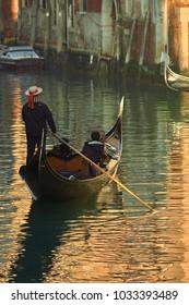 Italy, Venice, gondolier in the gondola at sunset