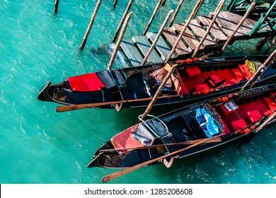 ITALY, VENICE - JANUARY 4, 2019: Traditional black gondolas of the city of Venice stand on the bright clear water at the pier.