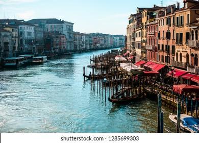 ITALY, VENICE - JANUARY 4, 2019: Venetian Grand Canal with old architecture along the coast, black gondolas.