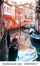 ITALY, VENICE - JANUARY 4, 2019:  A gondolier floats along a channel in a black gondola on a narrow channel along beautiful old architecture.