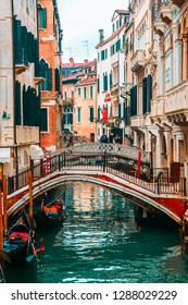 ITALY, VENICE - JANUARY 6, 2016:  Narrow street of the old city of Venice, canal with beautiful water, black gondolas.