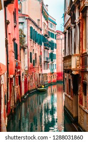 ITALY, VENICE - JANUARY 6, 2016:   The narrow water channel of the city of Venice against the background of bright red and orange apartment buildings.