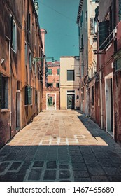 Italy, Venice - Jule 31, 2018: Narrow venetian streets, narrow lanes of Venice, Italy, alleys overlooking blue sky. - Filter applied in post-production by Yevheniy Myakiy