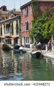 ITALY, VENICE - JULY 12, 2014: View of the streets, parked boats and leisure travelers.
