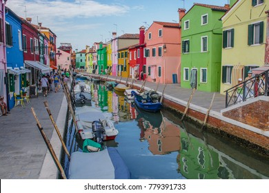 ITALY, VENICE - JULY 13, 2016: Street view to canal with lot of boats near brightly colored houses in Burano island