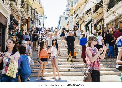 ITALY, VENICE - JUNE 19, 2014: The crowded Venice town crosswalk. Lots of people are strolling down the boardwalk. On the sides there are several shops against historical old stairway.