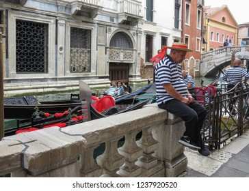 ITALY, VENICE - OCTOBER 15, 2014: Typical Venetian gondolier in traditional clothing is waiting for customers