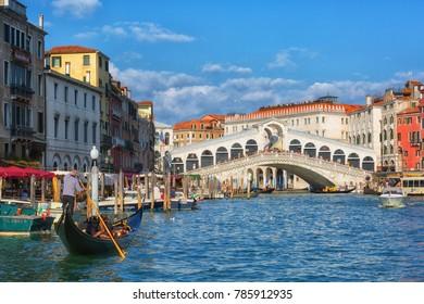 ITALY, VENICE - SEPTEMBER 26, 2017: Gondola with tourists on the Grand Canal near the Rialto Bridge