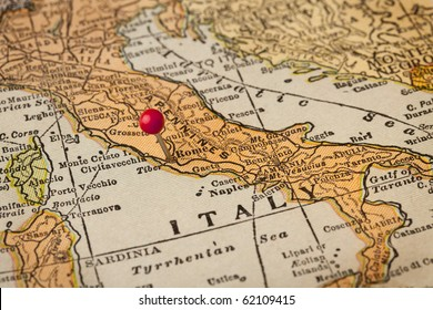 Italy vintage 1920s map (printed in 1926 - copyrights expired) with a red pushpin on Rome, selective focus