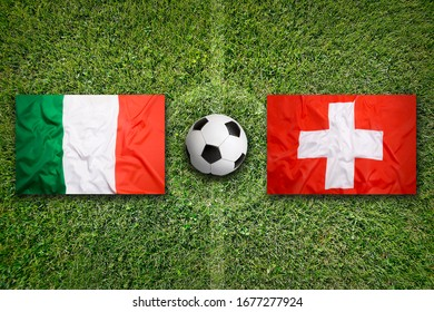 Italy vs. Switzerland flags on green soccer field