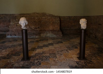 ITALY,BRESCIA - 26 June 2019: Brixia Archaeological Park of Brescia Romana. From left: head of Minerva white marble, head of Silenus white marble. Floor: geometrical pattern from marble